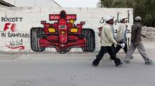 Men walk past anti-Formula One graffiti in the village of Barbar in Bahrain. (HAMAD I MOHAMMED/REUTERS)