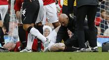 Manchester United's Wayne Rooney receives treatment on an injured knee before being stretchered off the pitch during their English Premier League soccer match against Fulham at Old Trafford in Manchester, northern England, August 25, 2012. (Phil Noble/REUTERS)