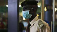 An immigration officer wears a face mask at the Nnamdi Azikiwe International Airport in Abuja, Nigeria, on 11, 2014. (AFOLABI SOTUNDE/REUTERS)