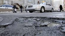 Motorists steer past a pothole on a Montreal street. The city's blue-collar workers, known over the years for their questionable productivity and strong-arm labour tactics, have shifted into a new role as shovel-wielding allies in the city's fight against corruption. (Paul Chiasson/CP)