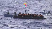 In this photo grabbed from footage released by the Italian Navy on Sunday, Oct. 13, 2013, migrants receive help from two raft from the Italian Navy ship Libra, off the Sicilian island of Lampedusa. Hundreds of migrants have drowned this month as smugglers' ships packed with migrants sank or capsized. (Associated Press)