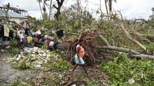 A woman examines the damage caused by Hurricane Matthew in her yard in Croix March-a-Terre, in southwest Haiti, on Oct. 6, 2016. (HECTOR RETAMAL/AFP/Getty Images)