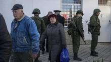 People walk outside the General Staff Headquarters of the Ukrainian Navy as unidentified gunmen stand outside it in Sevastopol, Ukraine, Monday, March 3, 2014. (Andrew Lubimov/AP)