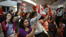 Canadian flags are waved during a citizenship ceremony at Seneca College in Markham, Ont. (FRED LUM/THE GLOBE AND MAIL)