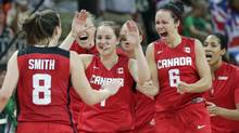 Canada's Kim Smith (8) is congratulated by Shona Thorburn, right, Courtnay Pilypaitis, center, and teammates after b
