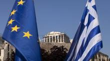 A European Union flag, left, hangs beside a Greek national flag beneath the Parthenon temple on Acropolis hill in Athens, Greece. Photographer: Simon Dawson/Bloomberg (Simon Dawson/Bloomberg)