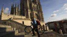 A man with a bike is walks in front of Burgos Cathedral in Burgos, Spain, Dec. 21, 2012. (GUILLERMO CERVERA/NYT)