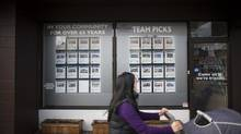 A woman walks past real estate listing posted in the window of a realty office in East Vancouver, British Columbia, Monday, November 4, 2013. (Rafal Gerszak For The Globe and Mail)