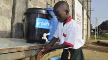 A boy washes his hands as part of Ebola prevention methods, before school starts in Paynesville, Liberia, November 24, 2015. (James Giahyue/Reuters)