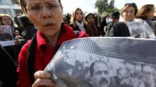 A woman carries a poster of assassinated politician Chokri Belaid, during a demonstration calling for Prime Minister Hamadi Jebali and his cabinet to step down, next to the National Constituent Assembly in Tunis on Feb. 11, 2013. (ANIS MILI/REUTERS)