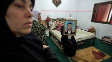 Latify Abu Shelbayeh holds a portrait of her husband Iyad, a Hamas member, in the bedroom of their home during his funeral in the Nour Shams refugee camp near the West Bank town of Tulkarm on Sept. 17, 2010. (Heidi Levine/Sipa Press)