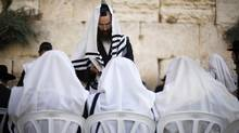 Jewish worshippers covered in prayer shawls pray at the Western Wall, Judaism's holiest prayer site, in Jerusalem's Old City on Sept. 4, 2013 ahead of Rosh Hashanah, the Jewish New Year which starts at sundown on Wednesday. (BAZ RATNER/REUTERS)
