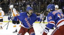 New York Rangers players Mats Zuccarello and Derick Brassard celebrate a goal by Benoit Pouliot during the second period of Game 7 of their first-round NHL series against the Philadelphia Flyers on Wednesday, April 30, 2014, in New York. (AP)