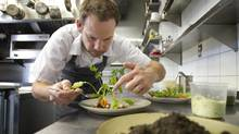 Chef Justin Cournoyer prepares a dish of radish and carrots with soil-infused butter at his restaurant Actinolite in Toronto. (Kevin Van Paassen For The Globe and Mail)