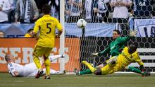 Columbus Crew's Dominic Oduro, right, of Ghana, blocks a shot by Vancouver Whitecaps' Kenny Miller, left, of Scotland, as Columbus' Danny O'Rourke, second left, watches in front of goalkeeper Andy Gruenebaum during the first half of an MLS game in Vancouver, B.C., on Saturday March 9, 2013. (DARRYL DYCK/THE CANADIAN PRESS)