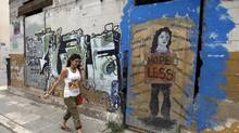 A woman walks past an abandoned building covered with graffiti in Athens on Wednesday, June 6, 2012. (JOHN KOLESIDIS/REUTERS)