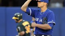 Toronto Blue Jays pitcher Brett Cecil stands behind the mound after giving up a two-run home run to Oakland Athletics batter Derek Norris (L) during the second inning of their MLB American League baseball game in Toronto July 24, 2012. (MIKE CASSESE/REUTERS)