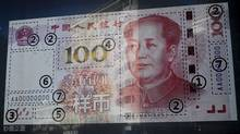 In this Monday, Jan. 11, 2016, file photo, an office building is reflected on a new 100 yuan note on display outside a bank in Beijing. (Andy Wong/AP Photo)