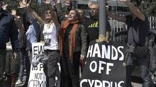 Demonstrators raise their arms in protest as Cypriot President Nicos Anastasiades's convoy drives to the parliament in Nicosia March 18, 2013. Cypriot ministers rushed on Monday to revise a plan to seize money from bank deposits as part of an EU bailout, in an effort to ensure lawmakers supported it in a vote later in the day. (YORGOS KARAHALIS/REUTERS)