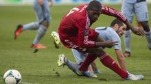 Toronto FC 's Doniel Henry (left) and Sporting Kansas City's Benny Felhaber battle for the ball during first half MLS action in Toronto on Saturday September 21, 2013. (CHRIS YOUNG/THE CANADIAN PRESS)