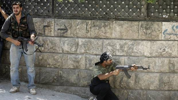 A Free Syrian Army fighter fires his rifle during clashes in Aleppo August 12, 2012. (GORAN TOMASEVIC/REUTERS)