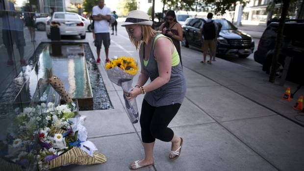 A fan brings flowers to a memorial for Glee actor Cory Monteith, who died Saturday, at the Fairmont Pacific Rim Hotel in Vancouver, British Columbia on July 14, 2013. (Rafal Gerszak for The Globe and Mail)
