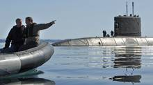 Prime Minister Stephen Harper and Defence Minister Peter McKay approach the submarine HMCS Cornerbrook in Frobisher Bay, off Baffin Island, on Aug. 19, 2009. (ANDY CLARK/REUTERS)