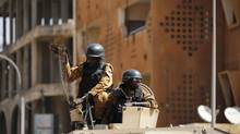 Soldiers stand guard in an armoured vehicle outside the Splendid Hotel after al Qaeda militants attack on the hotel and a restaurant in Ouagadougou, Burkina Faso. (Joe Penney/Reuters)