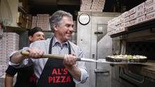Alberta PC Party party leader Jim Prentice loads a pizza in an oven during a campaign stop at Al's Pizza in Calgary, Alta., this week. (Jeff McIntosh/The Canadian Press)