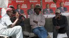 Supporters of presidential candidate Uhuru Kenyatta relax near his posters on a wall in Nairobi, March 7, 2013. (Sayyid Azim/AP)