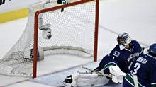 Puck goes past Vancouver Canucks goalie Roberto Luongo and into the net off the stick of San Jose Sharks Raffi Torres in overtime during Game 2 of their NHL Western Conference quarter final hockey playoff in Vancouver, British Columbia May 3, 2013. (ANDY CLARK/REUTERS)
