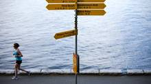 A jogger makes her way past signs informing people of various locations along Stanley Park's seawall in Vancouver, British Columbia, Wednesday, July 11, 2012. (Rafal Gerszak/The Globe and Mail)