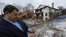 Toronto city councillor Mark Grimes takes photos of the demolition of the Casa Mendoza Inn on January 26, 2012. (Fred Lum/The Globe and Mail)