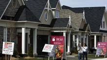 People walk past new homes that are for sale in Oakville, Ont. (NATHAN DENETTE)
