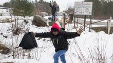An asylum claimant crosses the border into Canada from the United States on March 28 near Hemmingford, Que. (Paul Chiasson/The Canadian Press)