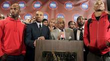 Surrounded by NBA basketball players, executive director of the National Basketball Players Association Billy Hunter, centre, and NBA Players Association president Derek Fisher, second from left, speak to the media during a news conference on Monday. (Seth Wenig/Associated Press)