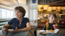 Premier Christy Clark sits with her son, Hamish, at the Vancouver airport in Richmond, B.C., before leaving on a holiday together (John Lehmann/The Globe and Mail)