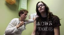 Nancy Brajtbord, RN, (L) administers a shot of gardasil, a Human Papillomavirus vaccine, to a 14-year old patient (who does not wish to be named) in Dallas, Texas March 6, 2007. (JESSICA RINALDI/Reuters)
