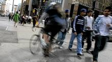 When cycling in heavy traffic, anticipate any trouble ahead. And no matter what, wear a helmet. (Peter Power/The Globe and Mail)