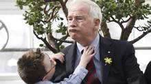 Cancer patient Michael Meehan, 7, adjusts Canadian Governor General David Johnston's tie during an event to mark the beginning of the Canadian Cancer Society's annual daffodil campaign at Rideau Hall in Ottawa April 1, 2014. (REUTERS/Chris Wattie)