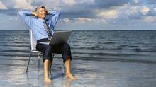 Businessman sitting on a chair on the beach with his hands behind his head. (George Doyle/Getty Images)