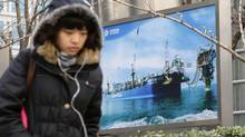 A woman walks past a poster showing an offshore work platform from the China National Offshore Oil Corp (CNOOC) next to its headquarters building in Beijing, December 10, 2012. (JASON LEE/REUTERS)