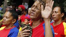 A woman holds a figurine of Venezuelan President Hugo Chavez, as she attends a mass to pray for Chavez's health in Caracas December 11, 2012. Chavez underwent surgery in Cuba on Tuesday for a cancer recurrence that has thrown his presidency into jeopardy and upended politics in the South American OPEC nation. (Carlos Garcia Rawlins/REUTERS)