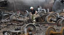 A police officer walks amongst axle gear in Lac Mégantic, Que., in this July 9, 2013 file photo. The Quebec government is seeking cleanup money from Canadian Pacific Railway, among others. (MATHIEU BELANGER/REUTERS)