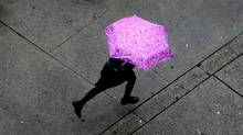 A young girl uses an umbrella to shield herself from the rain as she runs along Beatty St. near Robson St. at lunch time in Vancouver, on Friday October 8, 2010. (Darryl Dyck For The Globe and Mail/Darryl Dyck For The Globe and Mail)