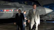 Defence Minister Peter MacKay and Industry Minister Tony Clement walk past a mock-up of the F-35 Joint Strike Fighter after announcing the Conservative government's plan to purchase 65 of the stealth jets in Ottawa on July 16, 2010. (Adrian Wyld/Adrian Wyld/The Canadian Press)