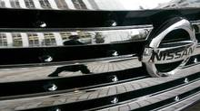 A man is reflected on a car from Nissan Motor Co. at the company headquarters in Tokyo. (Toru Hanai/Reuters)