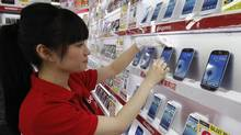 A saleswoman wipes the surface of Samsung's Galaxy S III smartphone, released by Japan's largest mobile carrier NTT Docomo Inc, at an electronics store in Tokyo on June 28, 2012. (Yuriko Nakao/Reuters)