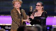 FILE- In this Jan. 25, 2015, file photo, Carrie Fisher, right, presents her mother Debbie Reynolds with the Screen Actors Guild life achievement award at the 21st annual Screen Actors Guild Awards at the Shrine Auditorium in Los Angeles. (Photo by Vince Bucci/Invision/AP, File)