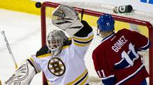 Boston Bruins goalie Tim Thomas reaches up to glove the puck as Montreal Canadiens' Scott Gomez looks for a rebound during second period NHL hockey action Wednesday, February 15, 2012 in Montreal. (Paul Chiasson/THE CANADIAN PRESS)